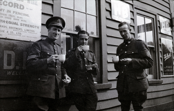 Norman Shepherd (right) and two other sergeants stand outside a wooden building at Kaitoke, drinking tea.