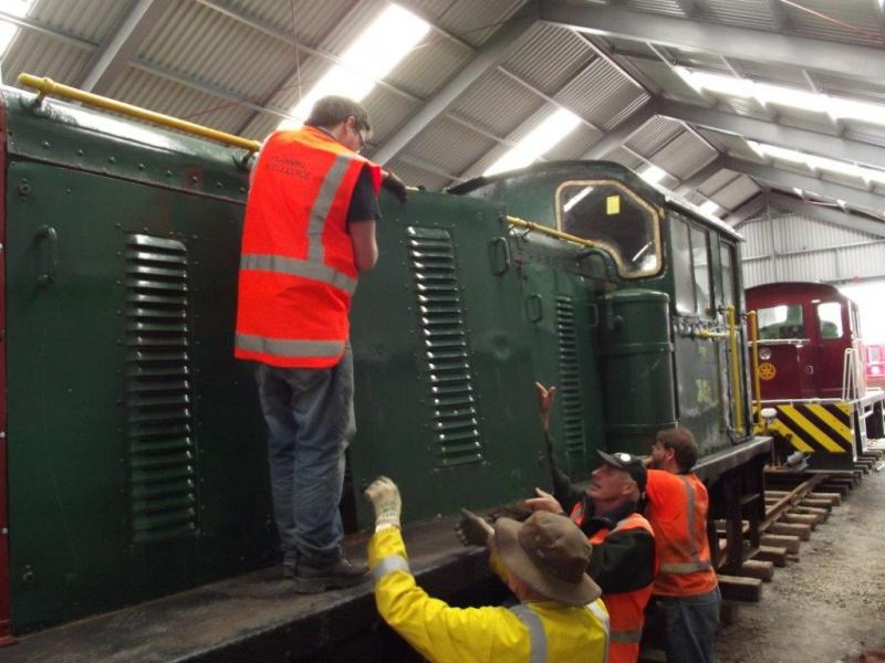Trust members checking over the locomotive, safely stored inside the rail vehicle shed.